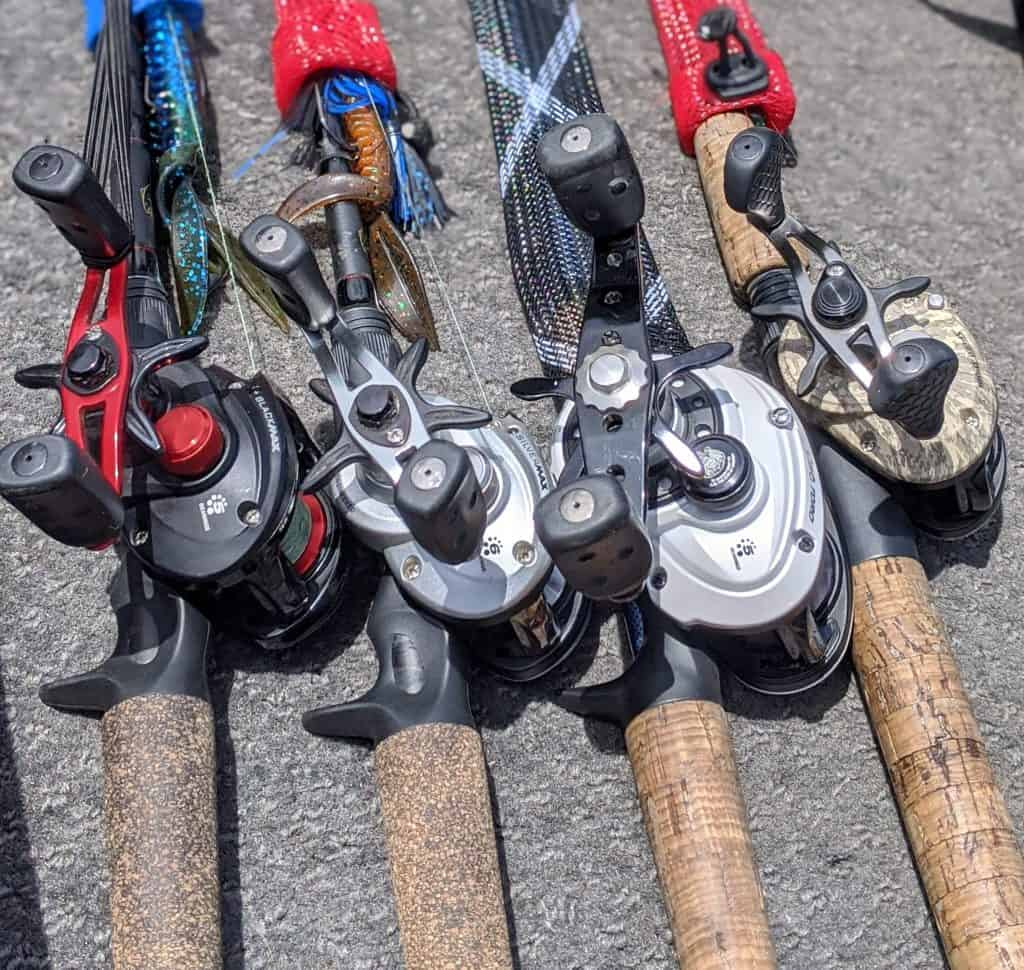 4 baitcaster reels setup for bass fishing laying on boat